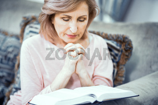 Beautiful mature woman is reading a book