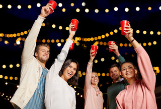 friends toasting party cups on rooftop at night