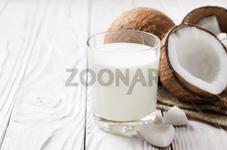 Drinking glass of milk or yogurt on hemp napkin on white wooden table with coconut aside
