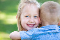 Young Brother and Sister Hugging At The Park