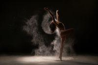 Gymnast dancing gracefully in white dust cloud