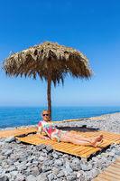 Woman sunbathes as tourist on stony european beach