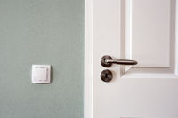 Modern white door with chrome door handle and light switch, new clean design