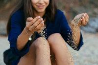 Detail of sand running through open hands.