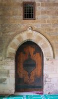 Vaulted closed decorated wooden grunge door in bricks stone wall