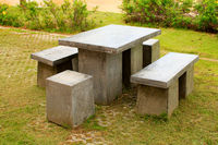 Stone benches table and stool at a garden in Phetchabun, Thailand.