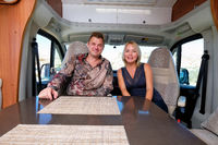 Married middle age couple sitting inside of recreational vehicle looking at camera. Active people lifestyle