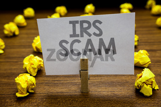 Word writing text Irs Scam. Business concept for targeted taxpayers by pretending to be Internal Revenue Service Clothespin hold holding paper idea reminder crumpled papers several tries.