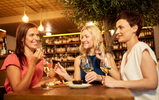 women eating snacks at wine bar or restaurant