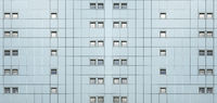 wide full frame facade of a modern building with geometric metallic cladding and lines of repeating pattern windows