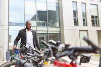 Afrikanischer Geschäftsmann mit Fahrrad vor Büro
