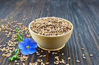 Flaxen brown seed in bowl with blue flower on board