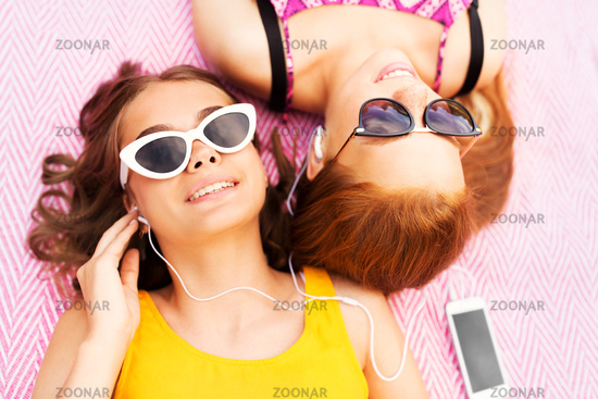 teenage girls listening to music from smartphone