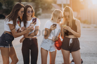 Four attractive women are standing on car parking with smartphones