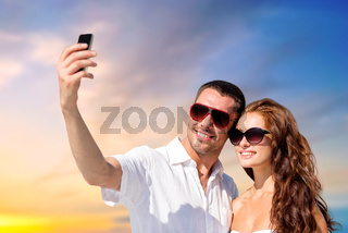smiling couple making selfie by smartphone