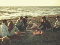 Friends having fun at beach on autumn day