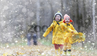Toddlers on a walk in the autumn park. First frost and the first