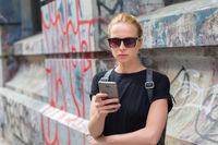 Woman using smartphones against colorful graffiti wall in New York city, USA.