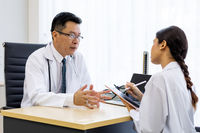 Two doctors in the hospital discuss the diagnos of the patient
