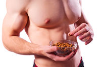 Sporty muscular man with almond nuts isolated
