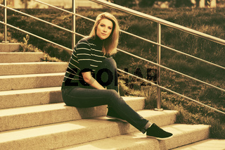 Young fashion woman in striped turtleneck t-shirt sitting on the steps