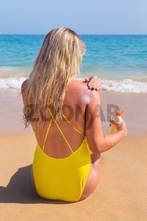 Blonde girl on beach smearing sunscreen on skin
