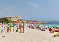 People enjoy summer holidays on the sandy beach Campoamor, Province Alicante, Spain