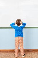Kind beim Nachdenken vor Whiteboard in Schule