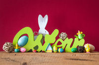 Word Easter in german language with easter bunny eggs and chicks