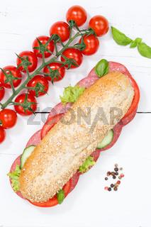 Sandwich Baguette Vollkorn Brötchen belegt mit Salami Hochformat von oben auf Holzbrett