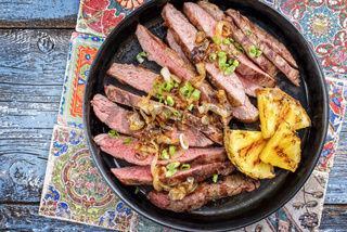Barbecue dry aged wagyu flank steak with pineapples and onion rings as top view on a plate