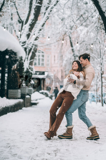 young guy and beautiful girl have fun on a snowy street. Couple in sweaters.