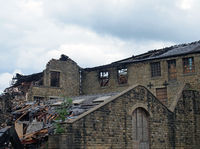 a large ruined industrial destroyed by a fire with collapsing walls and roof and burned timbers