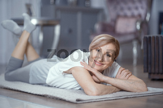 Mature woman is resting after practicing yoga