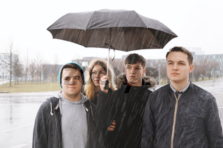 group of young urban teenage friends under one umbrella