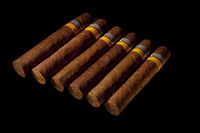 rolled cigars from a tobacco leaf on a black background