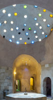 Arched stone wall lighted by glass roof holes at a historical traditional Turkish style public bath