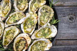 Barbecue overbaked fresh opened oyster with garlic and herbs offered as top view on a tray with copy space right