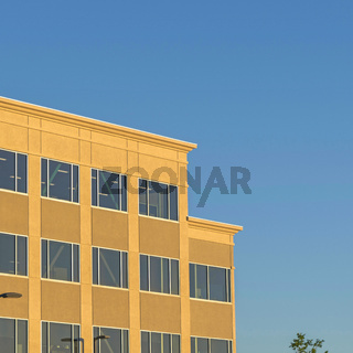 Square frame Commercial modern building exterior viewed against blue sky on a sunny day