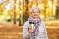 old woman with hot drink in tumbler at autumn park