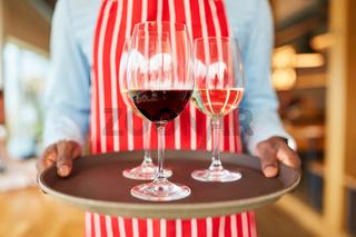 Hände eines Kellners tragen ein Tablett mit Wein