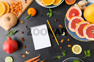 close up of notebook, fruits and vegetables