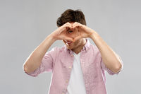 man making hand heart gesture over grey background