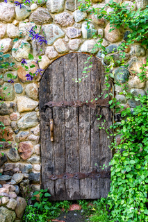Rough old wooden door with forged metal elements