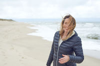 Smiling woman on a windy deserted beach