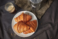 Coffee glass with freshly baked homemade croissants on a dark gray table