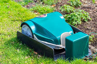 Green robotic Lawnmower charging on grass