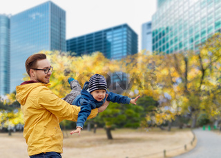 father with son having fun in autumn tokyo city