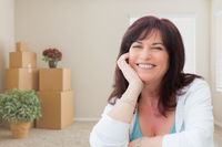 Middle Aged Woman Relaxing Inside Empty Room With Moving Boxes