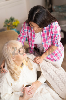 Daughter covers her senior mother with blanket